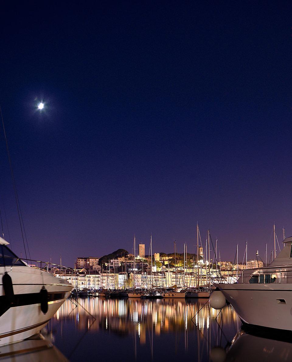 Vue sur le quartier du Suquet depuis le vieux port de Cannes de nuit