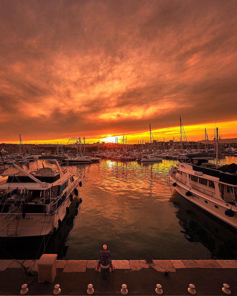 un homme sur le quai Henri Rambaud contemple le coucher du soleil au port Vauban d' Antibes