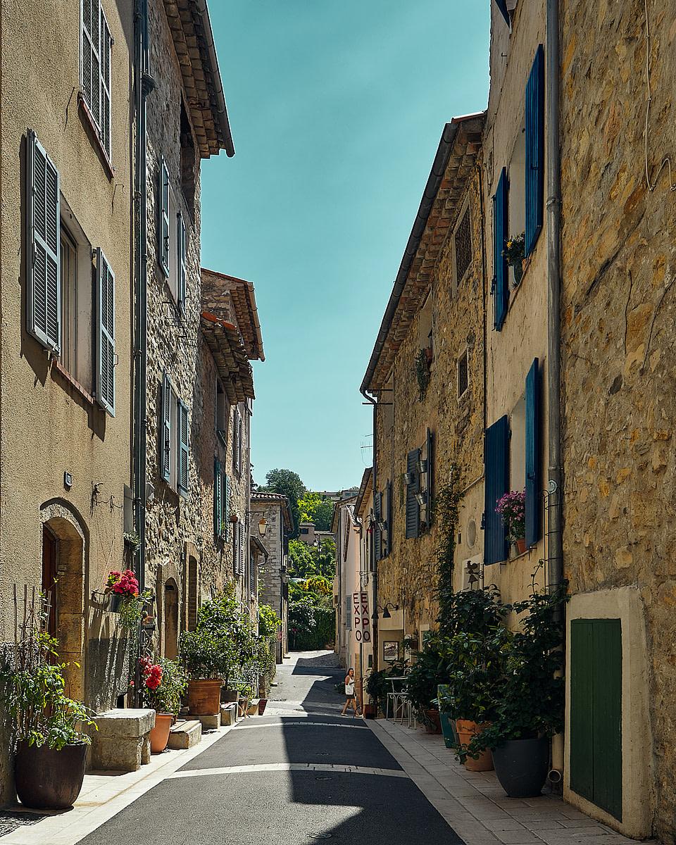Façade en pierre garnie de fleurs dans une ruelle ensoleillée à Valbonne - Cote d' Azur