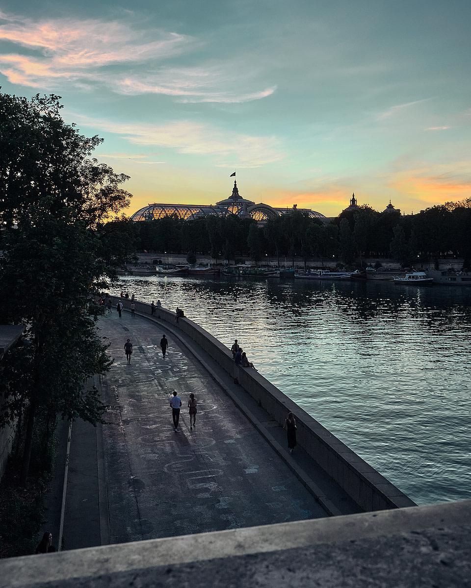 Des parisiens en soirée sur les berges de Seine face au Grand Palais depuis le Pont de la Concorde