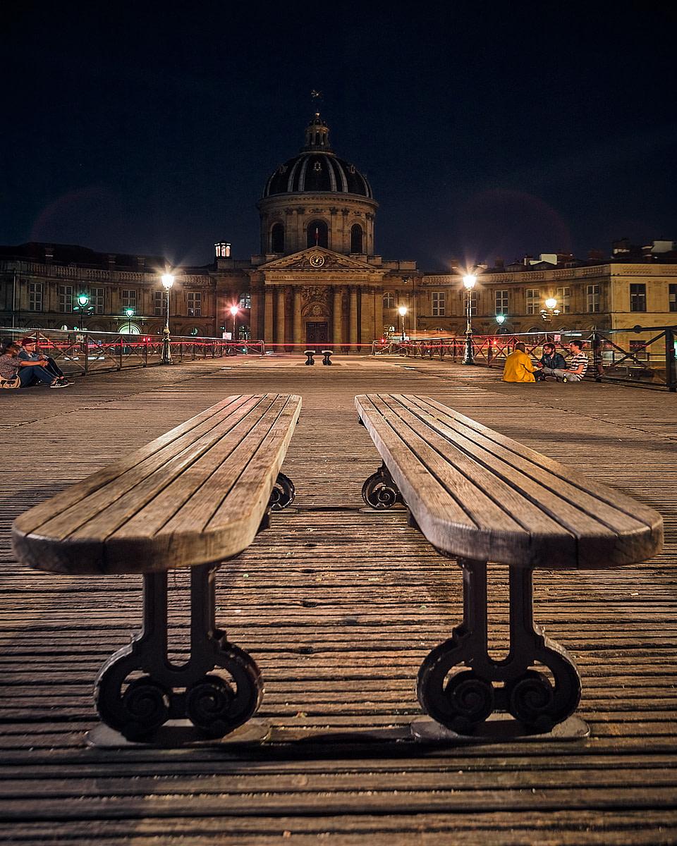 Duo de bancs sur le Pont des Arts avec vue sur l' institut de France de nuit à Paris
