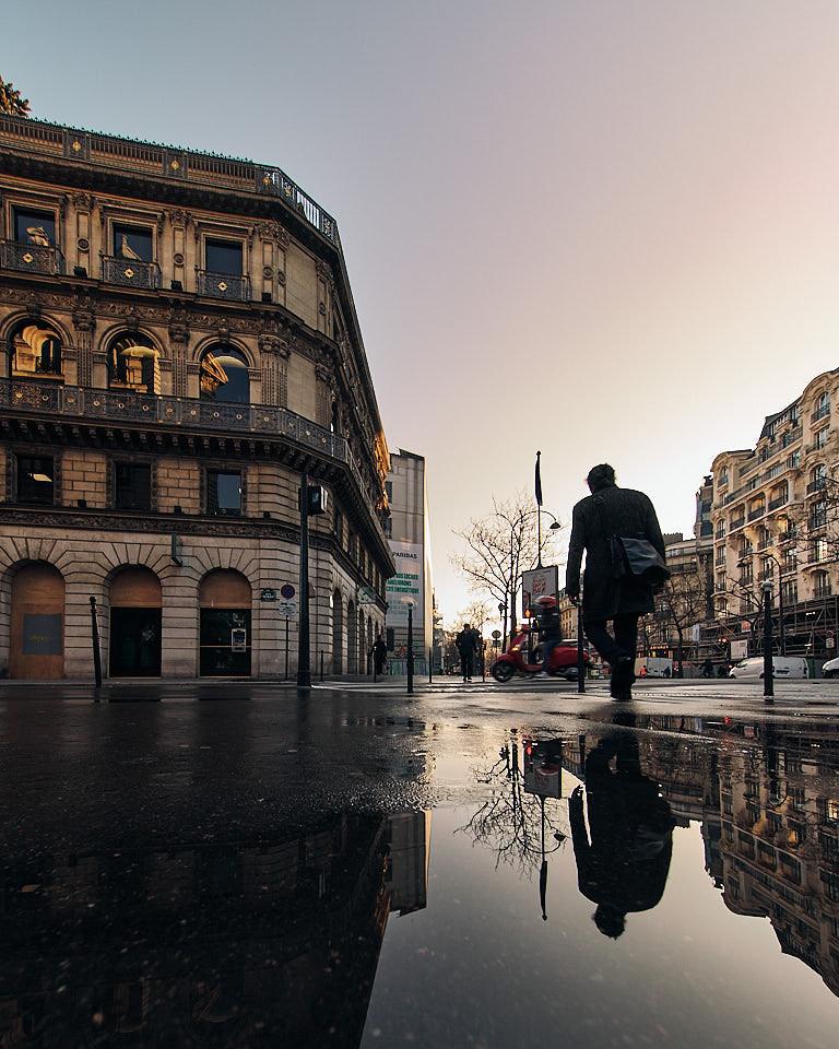 Pieton se reflète dans une flaque sur le Boulevard des Italiens à Paris au petit matin