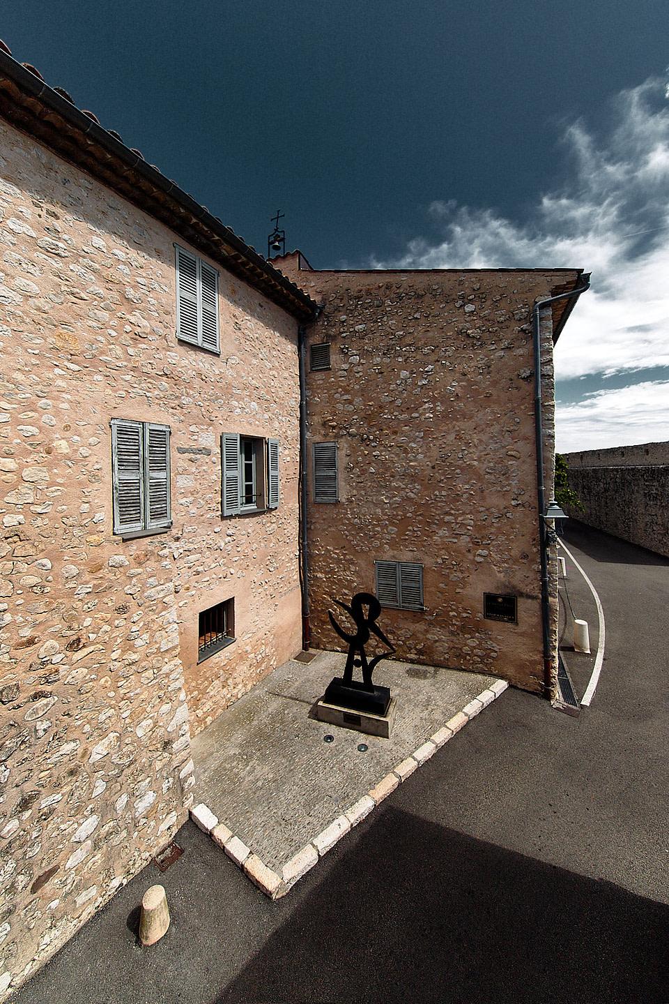 Une sculpture à l'angle de murs en pierre sous les remparts de Saint Paul de Vence