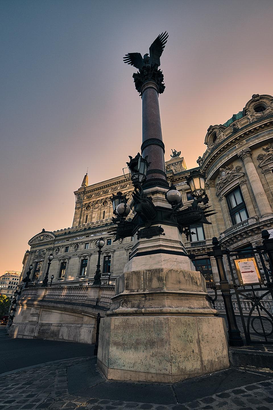 Depuis la rue Auber, le soleil se lève sur l'Opéra Garnier derriere une colonne qui porte un aigle impérial