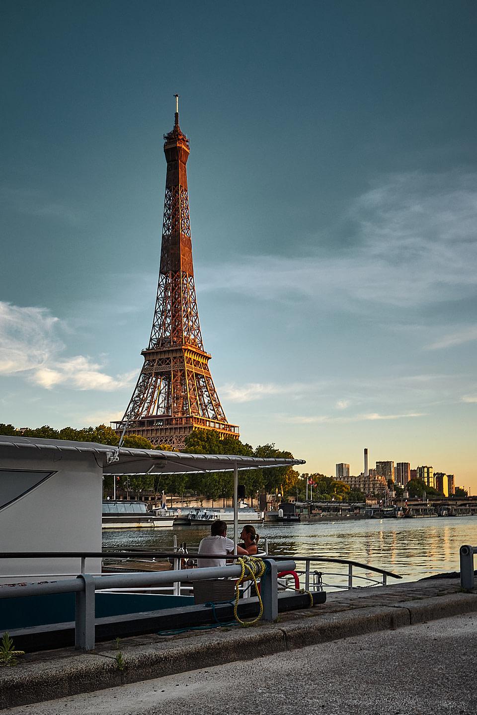 Un couple dans sa péniche devant la Tour Eiffel depuis le Port Debilly sur les berges de Seine à Paris