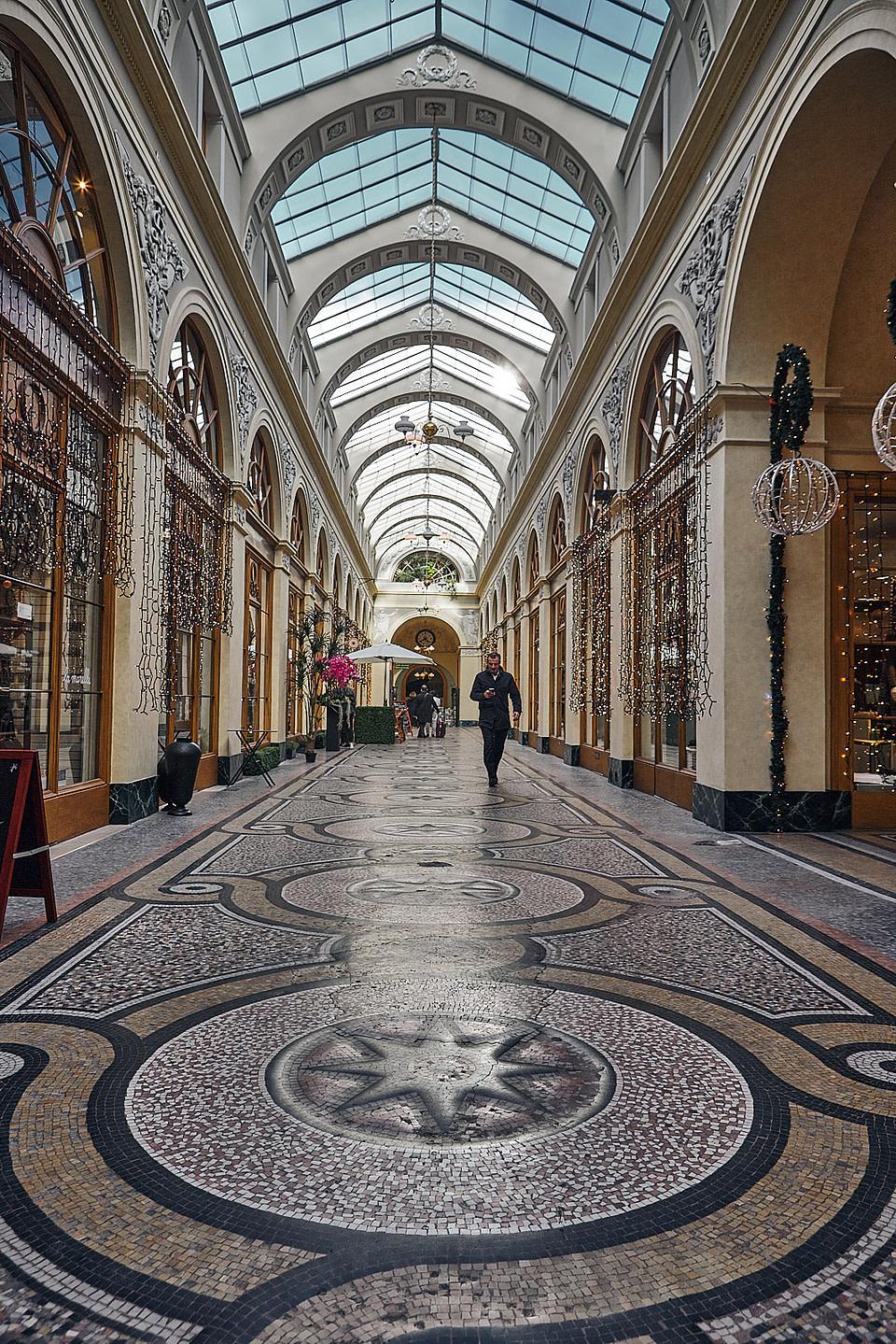 Un homme seul traverse la Galerie Vivienne à Paris