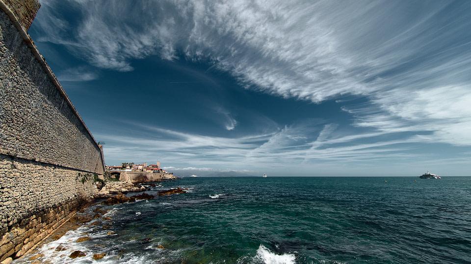 Vue sur les Remparts du Vieil Antibes en journée sous un ciel bleu avec des nuages étirés.