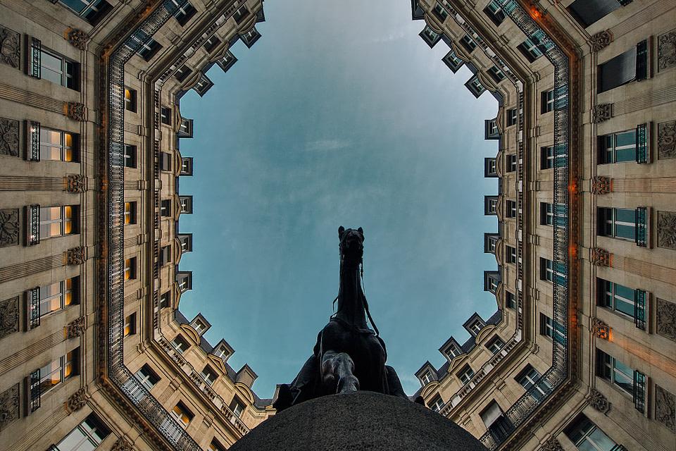 La Statue d' Edouard VII vue en contre plongée encadrée par les façades des immeubles de la Place Edouard VII à Paris