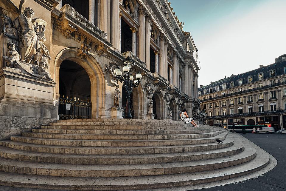 Une femme seule attend sur les marches de l'opéra Garnier