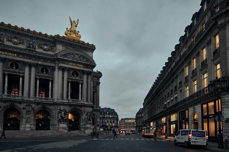 Les vitrines éclairées de la Rue Halevy devant la façade principale de l'Opéra Garnier à l'heure bleue