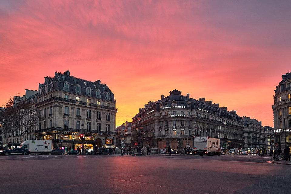 Le soleil se lève en colorant les nuage de rose sur les toits de la Place de l' Opéra