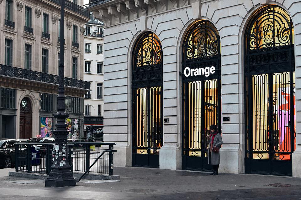 Une femme seule consulte son téléphone devant la boutique Orange rue Meyerbeer à Paris